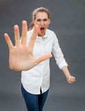 Furious young woman for self-defense, anger or rebellion. Furious young woman showing an over sized stopping hand in the foreground for self-defense, anger or Stock Photos