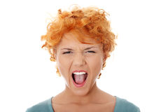 Furiouse young redhead woman screaming. Isolated on white stock photo