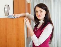 Furiture castana di pulizia della donna con lo straccio Fotografia Stock