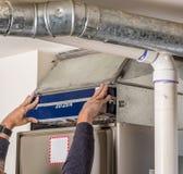 Furnace filter insertered my a handyman. Handyman inserts a furnace filter Royalty Free Stock Photos