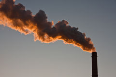 Dark smoke coming out from a polluting furnace Stock Image