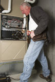 Furnace Repair. Repairman servicing or repairing basement furnace unit Stock Photo