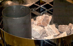 The furnace for sauna. Stones in the furnace of bath on a metal grate Royalty Free Stock Photos