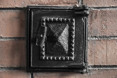 Furnance iron black door on red brick oven wall. Closeup Stock Image