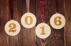 Furnieren Sie Weihnachtsbälle mit Nr. 2016 auf einem hölzernen Hintergrund Stockfotografie