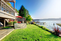 Furnished back patio with red chairs, grass, and water view. Wat Royalty Free Stock Images