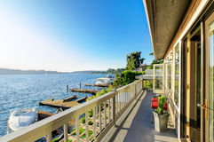 Furnished luxury back deck with red chairs, and water view. Lake Royalty Free Stock Image