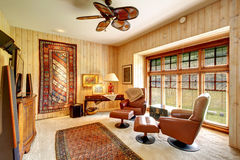 Furnished wood plank paneled room with rugs Stock Photo
