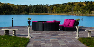 Furnitue group on a patio. Furniture group with lilac colored pillows on a paved patio. Beautiful view over a lake and autumn forest Royalty Free Stock Images