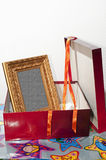 Furniture. Gift-wrapped package with an artistic gold-foil wooden frame inside Stock Photos