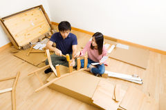Furniture assembling by asian couple Royalty Free Stock Photo