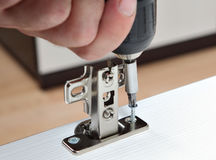 Furniture assembly, installation of door hinges, screws screwed Royalty Free Stock Images