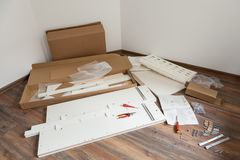 Furniture assembly parts and tools for self assembly furniture, on the floor. Stock Photos