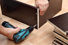 Furniture assembly using a cordless screwdriver, close up. Assembling furniture from chipboard, using a cordless screwdriver, close up stock image