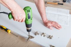 Furniture assembly using drill. Male hands master collects furniture using tools instrument drill in house. Moving, home