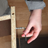 Furniture assembly, wood screw screwed  manually using allen ke Stock Photo