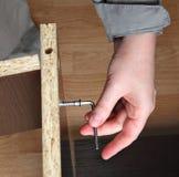 Furniture assembly, wood screw screwed manually using allen ke Stock Photo
