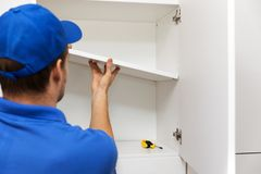 Furniture assembly - worker installing cabinet shelf. Furniture assembly - worker in blue uniform installing cabinet shelf stock images
