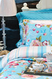 Furniture and bedding. Furniture and blue color bedding, and colorful tea set on bed, shown as comfortable life Stock Photography