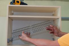 Furniture canopies can be screwed with screws to the closet door, close-up. Installing a stainless mesh for drying dishes in the kitchen cupboard royalty free stock image