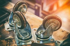 Furniture caster wheel. Made from metal and plastic on wooden table, Industrial spinning wheel stock photo