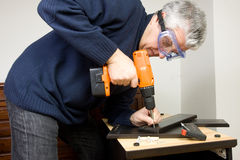 Furniture fitter. A man working as a jointer fitting some furniture Royalty Free Stock Image