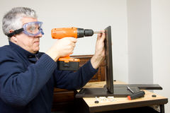 Furniture fitter. A man working as a jointer fitting some furniture Royalty Free Stock Images