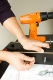 Furniture fitter. Building a desk with several tools of work Royalty Free Stock Photos