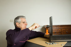 Furniture fitter. Building a desk with several tools of work Royalty Free Stock Image