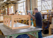 Furniture frame builder;. Na horizontal photograph taken in a furniture factory of a man building sofa frame out of plywood;n Stock Images