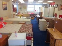 Furniture inside a second hand used charity shop. Used furniture for sale in charity shop. Second hand furniture donated for charity Stock Photo