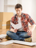 Furniture installation. Concentrated young man reading the instructions to assemble furniture in the kitchen at home Stock Image