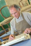 Furniture maker chiselling chair joint in workshop. Furniture maker chiselling a chair joint in his workshop Royalty Free Stock Photography