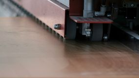 Furniture manufacture. Machine for edging chipboard parts. Worker`s hands guide the part for gluing the edge. Selective focus. Clo