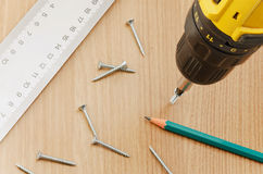 Furniture manufacturing. Carpentry tools and a drill to make holes in the furniture parts chipboard Stock Photos