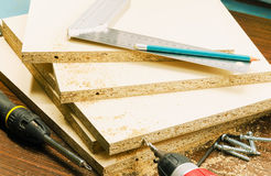Furniture manufacturing. Carpentry tools and a drill to make holes in the furniture parts chipboard Royalty Free Stock Photos