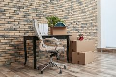 Furniture and moving boxes in office. Furniture and moving boxes in empty office stock photos