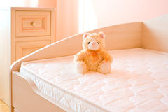 Furniture in the nursery. The furniture in the nursery: a mattress with a teddy bear and a bedside table Royalty Free Stock Photos
