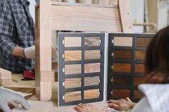 Furniture production master making wooden chair, female designer with wood samples choosing finishing in woodworking workshop royalty free stock photos