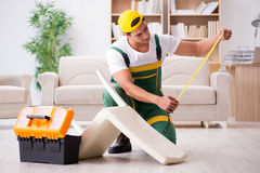 The furniture repairman repairing armchair at home. Furniture repairman repairing armchair at home Royalty Free Stock Photography