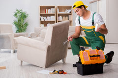 The furniture repairman repairing armchair at home. Furniture repairman repairing armchair at home Stock Photo