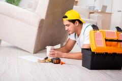 The furniture repairman repairing armchair at home Stock Image