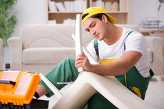 The furniture repairman repairing armchair at home Stock Photos