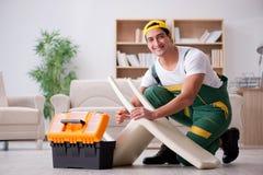 The furniture repairman repairing armchair at home Stock Photo
