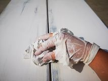 Furniture restoration and worker s hands in a dirty broken rubber gloves. Worker s hands in a dirty broken rubber gloves royalty free stock photo