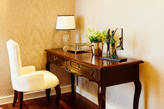 Furniture in room. A view of typical furniture in a hotel room including a desk and chair, chest of drawers and a crystal desk lamp Stock Photos