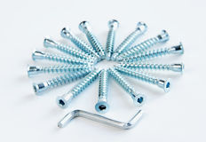Furniture screws and six-sided key. Lie on the light background Royalty Free Stock Photos