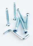 Furniture screws and six-sided key. Lie on the light background Stock Images