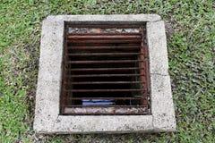 Furo da drenagem que raspa para a sujeira velha, cimento do desperdício sujo da água no assoalho do gramado, cimento da água da t imagem de stock royalty free