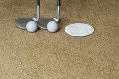 Furo das bolas de golfe dos clubes de golfe em um tapete Fotografia de Stock Royalty Free